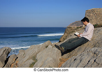 Relaxation - Young man reading a book on a rock with a great...