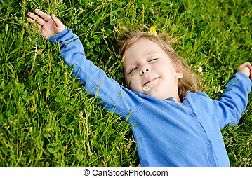 toddler girl relaxing on the meadow