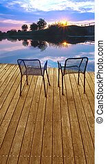 Two empty chairs on a boardwalk during sundown on a lake