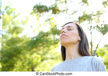 Relaxed adult woman breathing deep fresh air standing in a forest