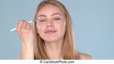 Relaxed and happy caucasian woman applying makeup on her ...