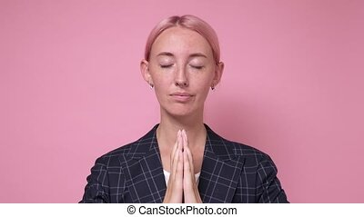 Relaxed and patient smiling young woman with closed eyes meditating to calm down, do breathing exercises with palms together. Studio shot on pink wall.