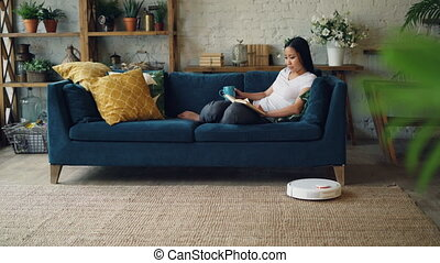 Relaxed Asian woman is reading book turning pages sitting on...