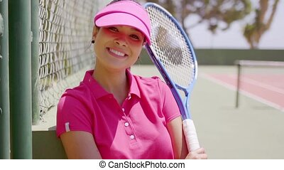 Relaxed attractive female tennis player standing with her...