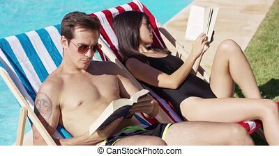 Relaxed attractive young couple reading poolside reclining...