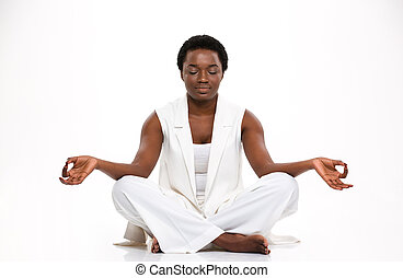 Relaxed beautiful african woman sitting and meditating in yoga pose
