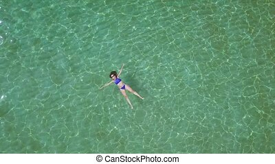 Relaxed beautiful girl lies on her back in the summer sea -...