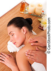 Relaxed beautiful young woman having a spa massage on her back