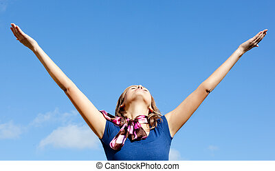Relaxed blond woman punching tha air against blue sky -...