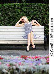 Relaxed blonde sitting on bench