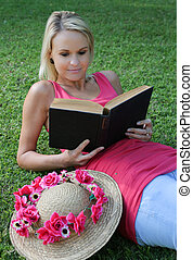 Pretty young woman reclining on the grass while reading a book