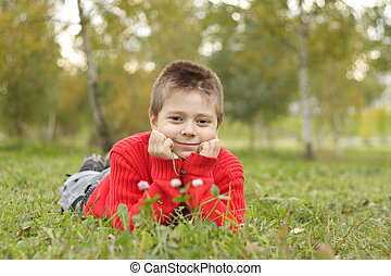 Relaxed boy laying on grass
