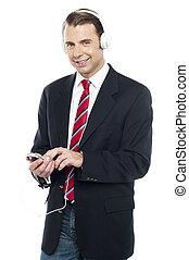 Relaxed business executive tuned into music, wearing...