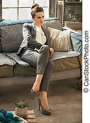 Relaxed business woman sitting on sofa in loft apartment