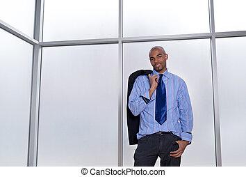 Relaxed businessman beside a big office window