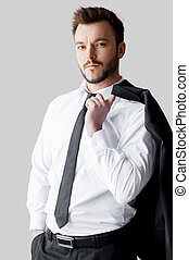 Relaxed businessman. Handsome young man in formalwear holding his jacket on finger and looking at camera while standing against grey background