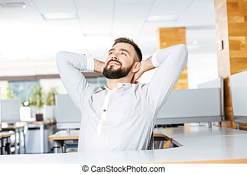Relaxed businessman sitting in office with hands behind head
