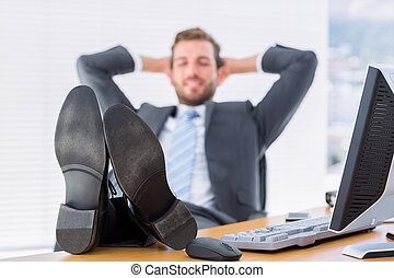Relaxed businessman sitting with legs on desk at office