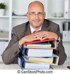 relaxed businessman with a stack of binders