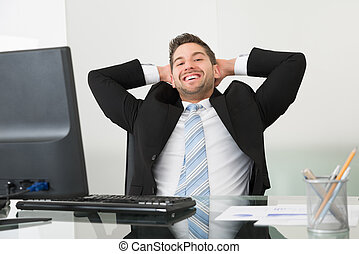 Relaxed Businessman With Hands Behind Head At Desk