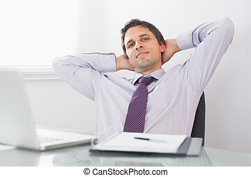 Relaxed businessman with hands behind head in office