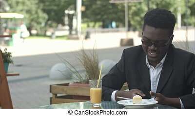 Relaxed carefree young afro american man in stylish eyewear sitting alone at cafe table, using smart phone, reading text message with joyful smile during lunch