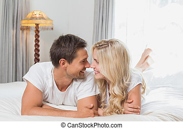 Relaxed casual young couple resting in bed