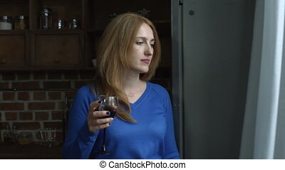 Relaxed cheerful woman tasting red wne at home