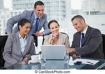 Relaxed colleagues analyzing documents on their laptop