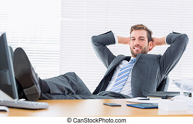 Relaxed confident businessman sitting with legs on desk