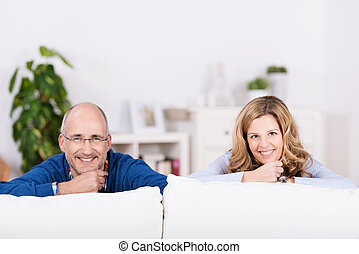 Relaxed confident smiling man and woman relaxing at home in...