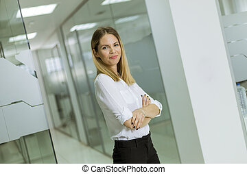 Relaxed confident young businesswoman standing standing in the modern office