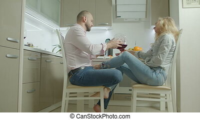 Relaxed couple drinking red wine in the kitchen