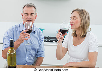 Relaxed couple drinking wine in kitchen