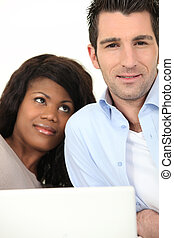 Relaxed couple in front of laptop