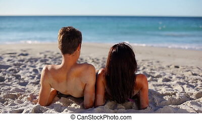 Relaxed couple lying on sand
