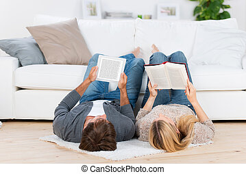 relaxed couple lying on the floor reading - relaxed couple...