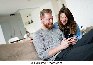Relaxed couple or friends using mobile phone together to shop online