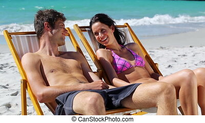 Relaxed couple sitting on deck chairs on the beach