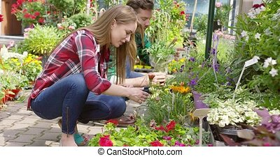 Relaxed couple spending time in gardening - Side view of...