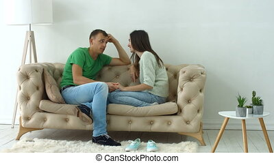 Relaxed couple talking together sitting on sofa