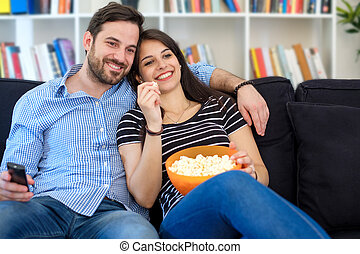 Relaxed couple watching movie on the television
