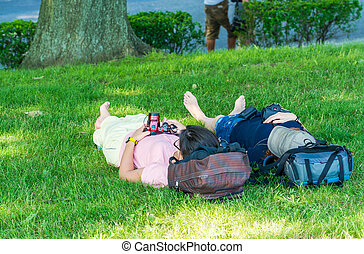 Relaxed couple with cameras laying on the grass