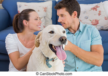 Relaxed couple with pet dog sitting in living room
