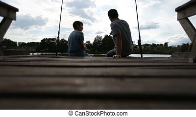 Relaxed dad and son bonding while angling on lake