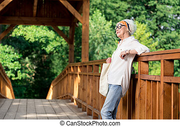 Relaxed elderly woman standing on the bridge and waiting for her husband