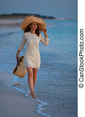 relaxed elegant woman on seacoast at sunset walking