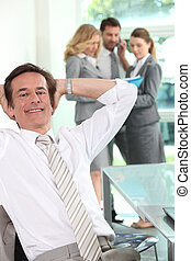 Relaxed executive in the office with his colleagues in the background