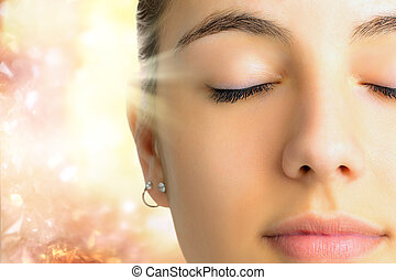 Relaxed face shot of woman meditating.