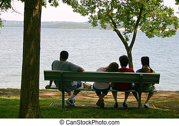 A vacationing family sitting on a park bench by the lake